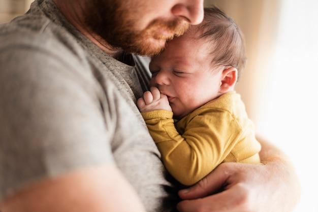 Close-upvader die zijn baby koestert Gratis Foto