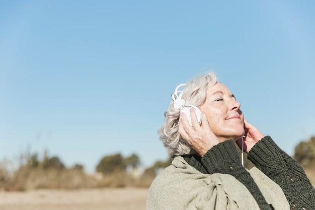 Close-upvrouw die aan muziek luisteren Gratis Foto