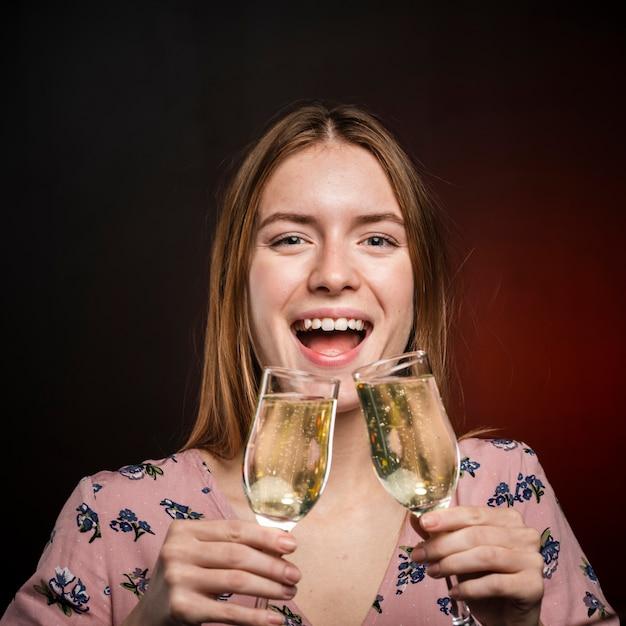 Close-upvrouw die champagne van twee glazen proberen te drinken Gratis Foto