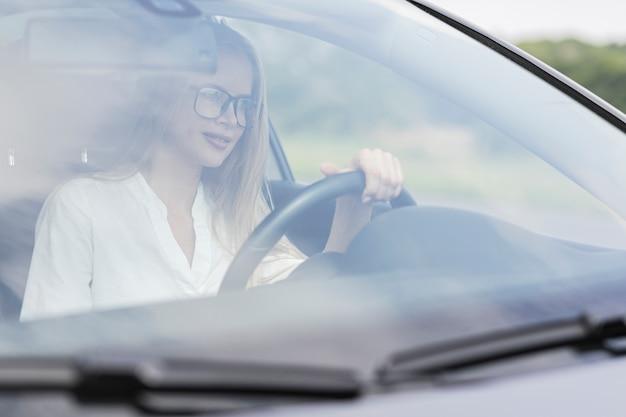 Close-upvrouw die de auto drijven Gratis Foto