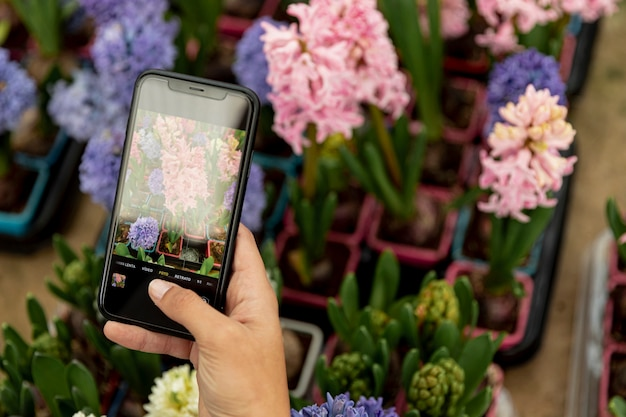 Close-upvrouw die een foto van bloemen nemen Gratis Foto