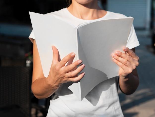 Close-upvrouw die een modeltijdschrift lezen Gratis Foto