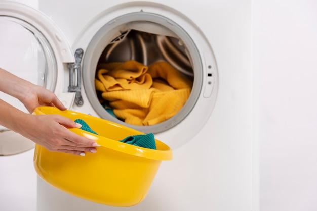 Close-upvrouw die kleren nemen uit wasmachine Gratis Foto