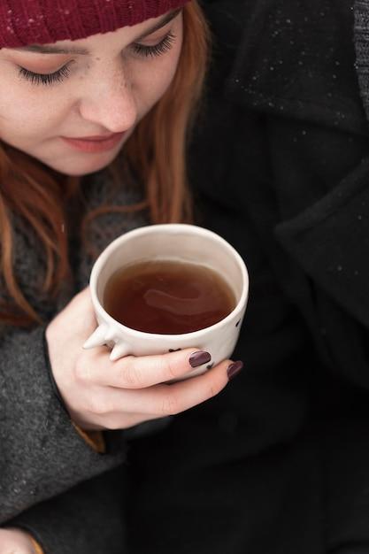 Close-upvrouw die met de winterkleren kop thee houden Gratis Foto