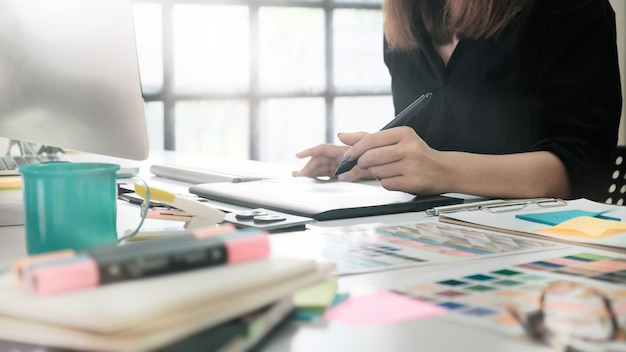 Close-upvrouw die met schets aan digitale lijst, grafische ontwerper werken die aan lijst werken. Premium Foto