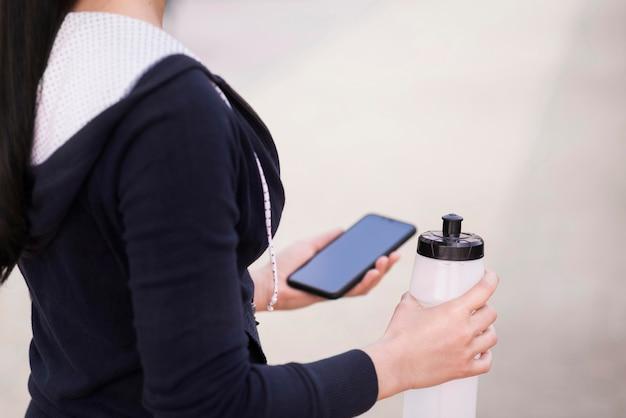 Close-upvrouw die mobiele telefoon en waterfles houden Gratis Foto