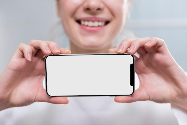 Close-upvrouw die mobiele telefoon houden Gratis Foto