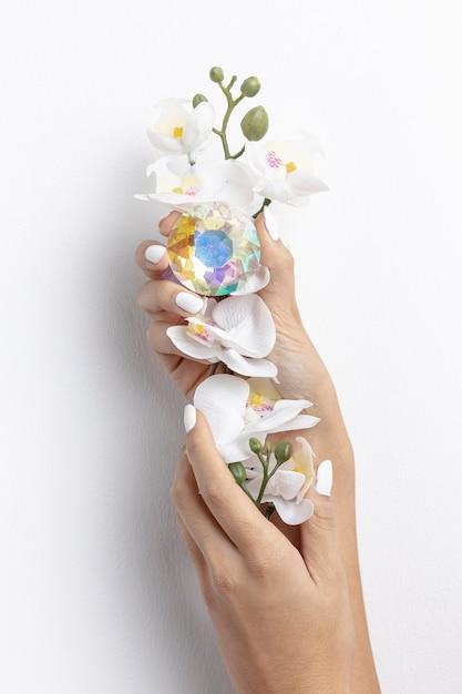 Close-upvrouw die mooi bloem en kristal houden Gratis Foto