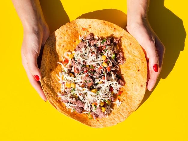 Close-upvrouw die ongevouwen burrito houden Gratis Foto
