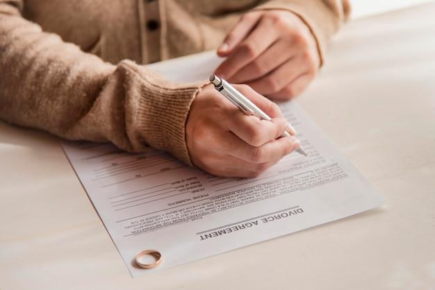 Close-upvrouw die scheidingsovereenkomst ondertekenen Gratis Foto
