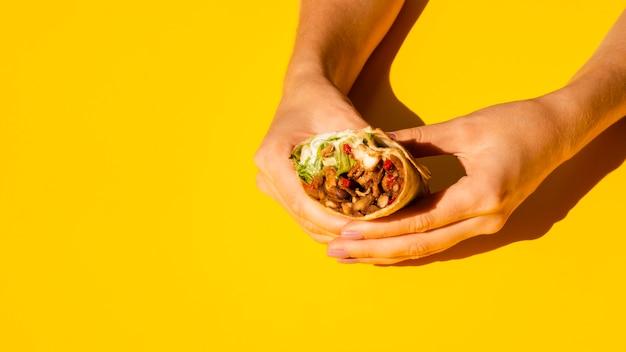 Close-upvrouw die smakelijke burrito houden Gratis Foto