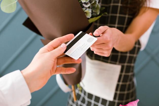 Close-upvrouw die voor boeket met creditcard betalen Gratis Foto