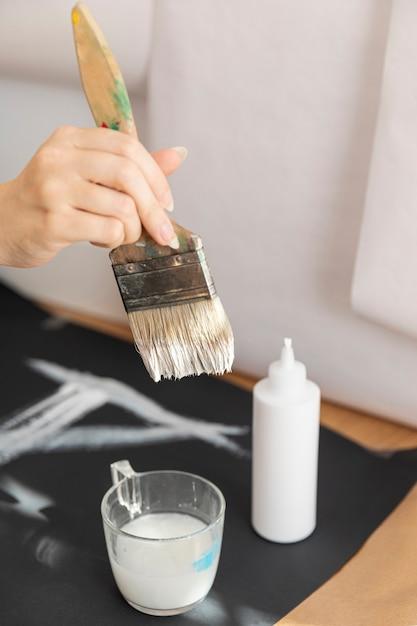 Close-upvrouw die witte verf en borstel gebruiken Gratis Foto