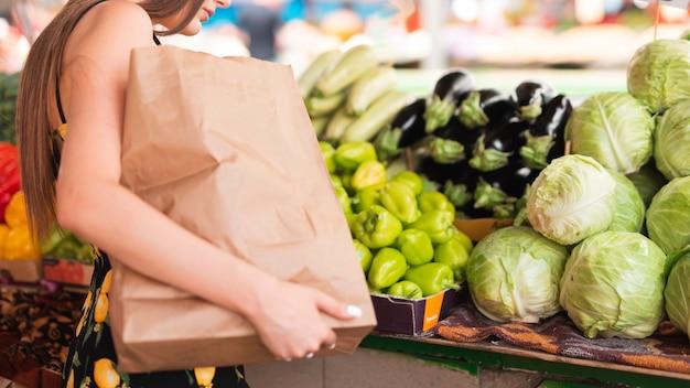 Close-upvrouw het winkelen kruidenierswinkels Gratis Foto