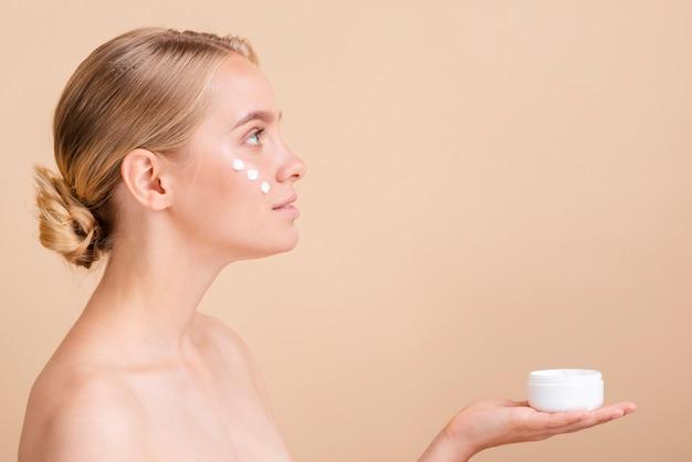 Close-upvrouw met gezichtsroom en kruik Gratis Foto