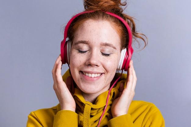 Close-upvrouw met hoofdtelefoons en brede glimlach Gratis Foto