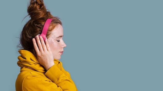 Close-upvrouw met hoofdtelefoons en exemplaar-ruimte Gratis Foto