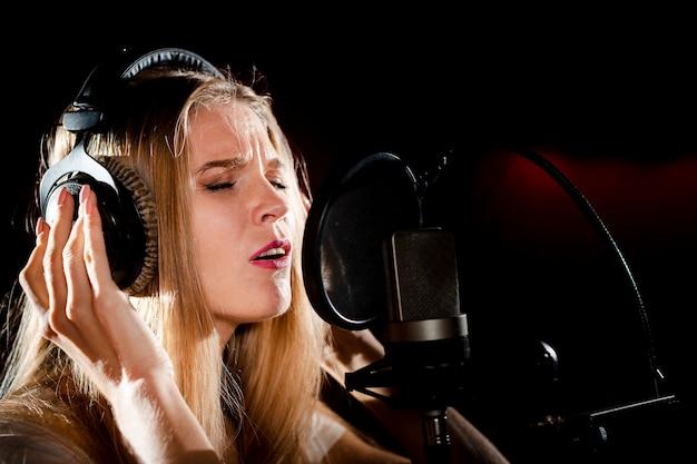 Close-upvrouw met hoofdtelefoons het zingen Gratis Foto
