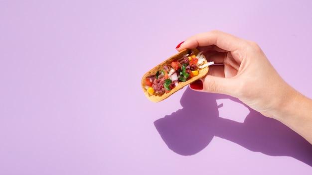Close-upvrouw met taco, exemplaar-ruimte en purpere achtergrond Gratis Foto