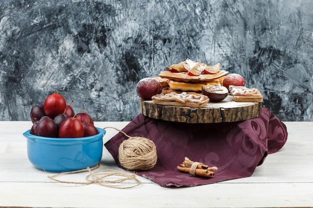 Close-upwafels en koekjes op ronde rieten placemat met een kom pruimen, bordeauxrood tafelkleed en kluwen op donkerblauw marmer en wit houten plankoppervlak. horizontaal Gratis Foto