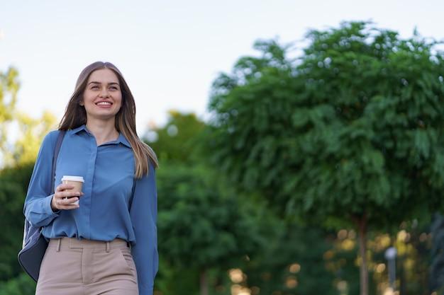 Closeup aantrekkelijke vrouw in beweging met afhaalmaaltijden koffie op straat. portret blond meisje papier beker met warme drank buiten houden. Gratis Foto