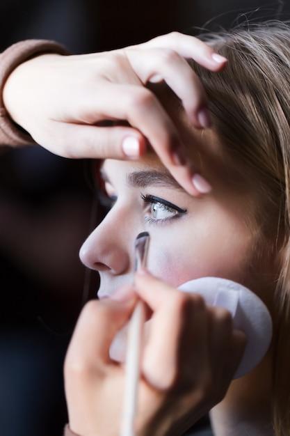 Closeup blonde jonge dame bereid door make-up artiest Premium Foto