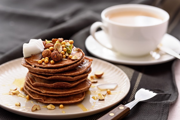 Closeup chocolade pannenkoeken met kiwi, hazelnoot, honing, kokosvlokken op plaat met vork en kopje thee of koffie op grijze handdoek achtergrond Premium Foto