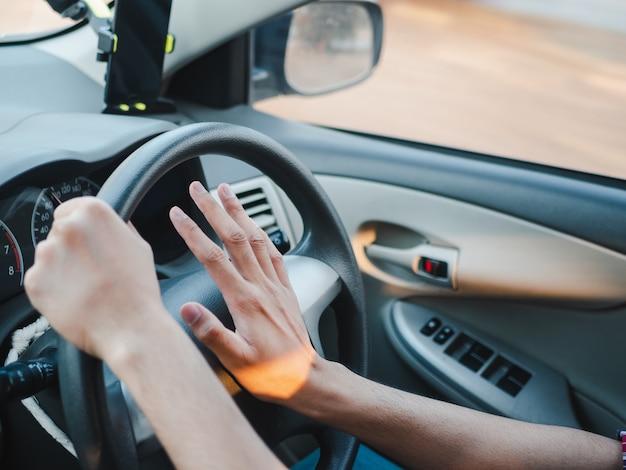 Closeup driver's hand te drukken op een auto hoorn tijdens het rijden Premium Foto