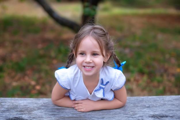 Closeup portret gelukkig lachend meisje met grote ogen en twee vlechten op haar hoofd in de tuin. glimlachend mooi kind. Premium Foto