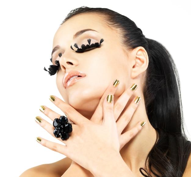 Closeup portret van de mooie vrouw met lange zwarte valse wimpers make-up en gouden nagels. geïsoleerd op een witte muur Gratis Foto