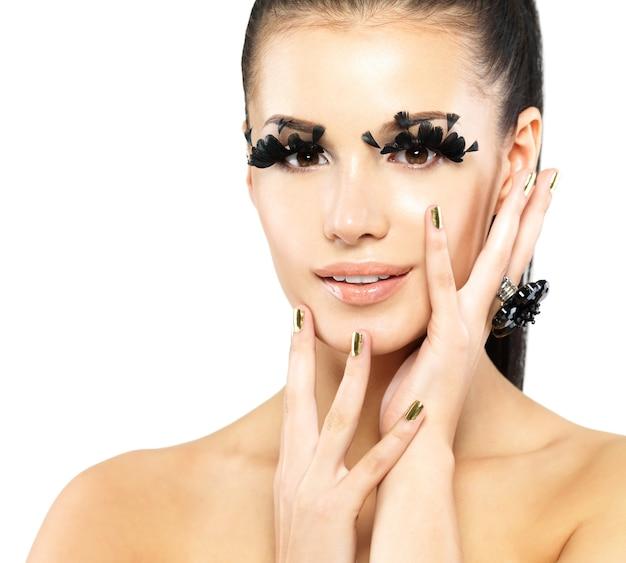 Closeup portret van de mooie vrouw met lange zwarte valse wimpers make-up en gouden nagels. geïsoleerd op witte achtergrond Gratis Foto