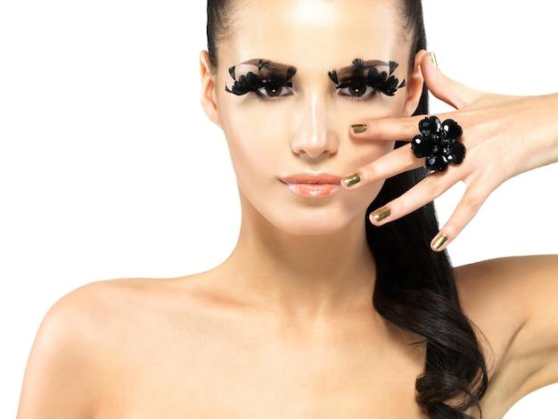 Closeup portret van de mooie vrouw met lange zwarte valse wimpers make-up en gouden nagels. Gratis Foto