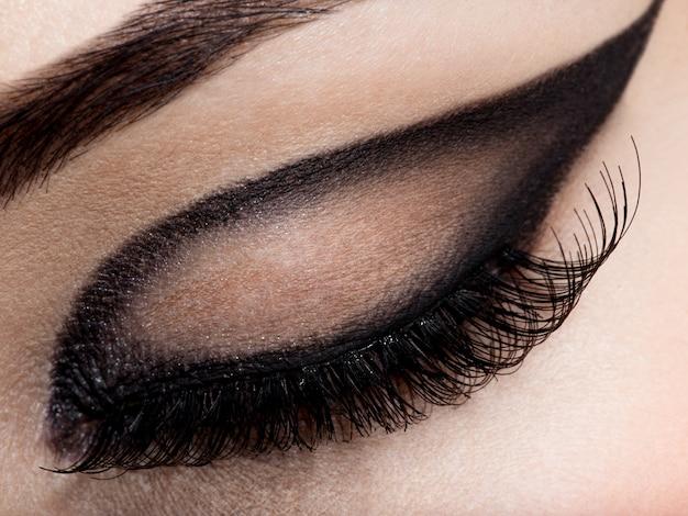 Closeup vrouwelijk oog met creatieve fashion make-up. bruine oogschaduw Gratis Foto