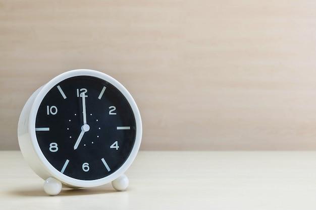 Closeup wekker voor decoreren in 7 uur op houten bureau en muur achtergrond Premium Foto