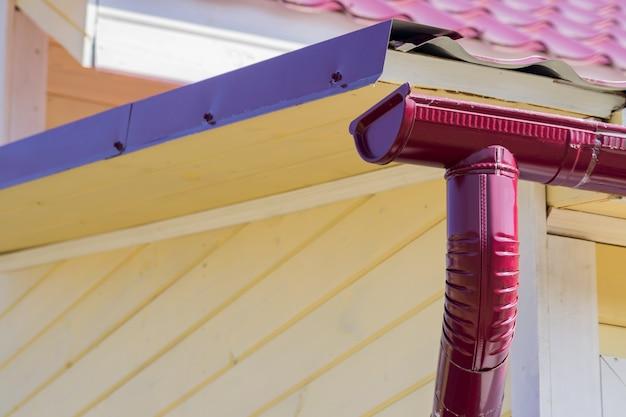 Clsoe omhoog van rode goot op het dak van huis Premium Foto