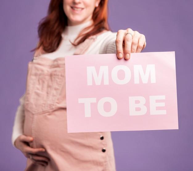 Clsoe-up zwangere vrouw met papier met moeder om bericht te zijn Gratis Foto