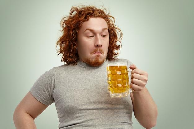 Clueless roodharige jonge man met krullend haar met glas licht bier, kijkend naar het, verward besluiteloze aarzeling, aarzelend, denkend drink het of niet, staand tegen blinde muur Gratis Foto