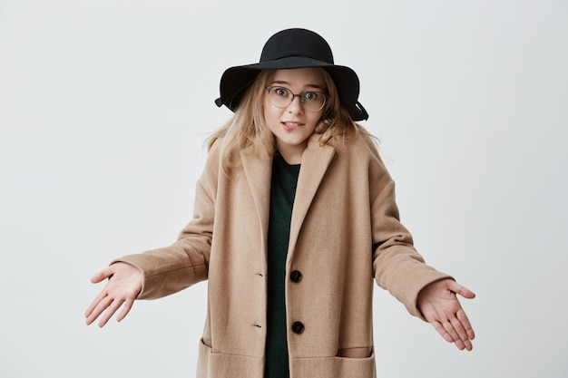 Clueless twijfelachtig ontevreden vrouw in jas, bril en zwarte hoed die schouders ophaalt in onzekerheid, aarzelt of ze op feest of date gaan. aarzelende jonge vrouw weet niet hoe het toekomstige leven verandert Gratis Foto