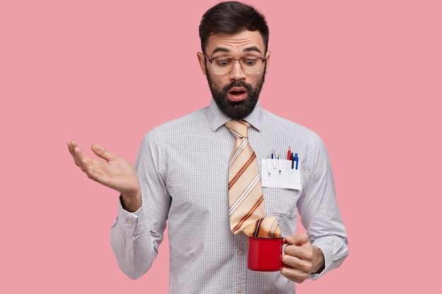 Clueless verrast man met dikke haren, steekt hand op, kijkt verontwaardigd naar beker met stropdas, gekleed in formele kleding Gratis Foto