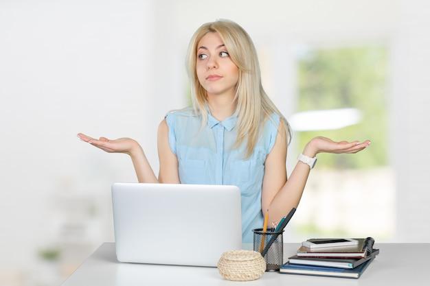 Clueless vrouwelijke student met laptop Premium Foto