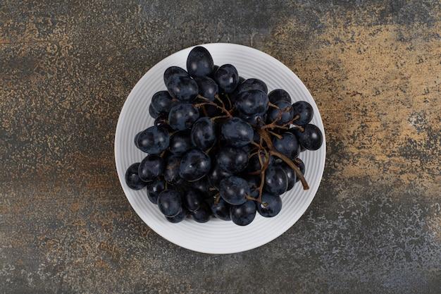 Cluster van zwarte druiven op witte plaat. Gratis Foto