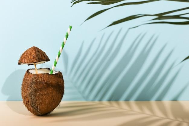 Cocktail in een open kokosnoot en de schaduw van palmbladen op gekleurd. zomerstemming, oogsten. Premium Foto