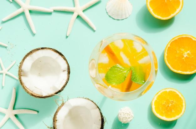 Cocktail met sinaasappel, munt en ijs in de buurt van kokosnoten Gratis Foto