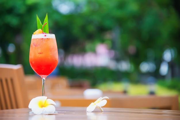 Cocktail receptnaam mai tai of mai thai wereldwijde cocktail onder meer rum limoensap orgeatsiroop en sinaasappellikeur - zoete alcoholische drank met bloem in tuin relax vakantie concept Gratis Foto