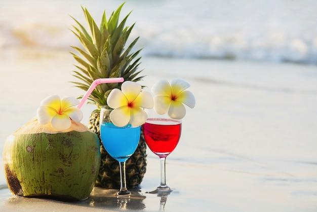 Cocktailglazen met kokosnoot en ananas op schoon zandstrand - fruit en drank op overzees strand Gratis Foto