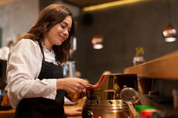 Coffeeshopmedewerker die koffie maakt Gratis Foto