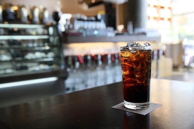 Cola op hout met restaurantachtergrond Premium Foto