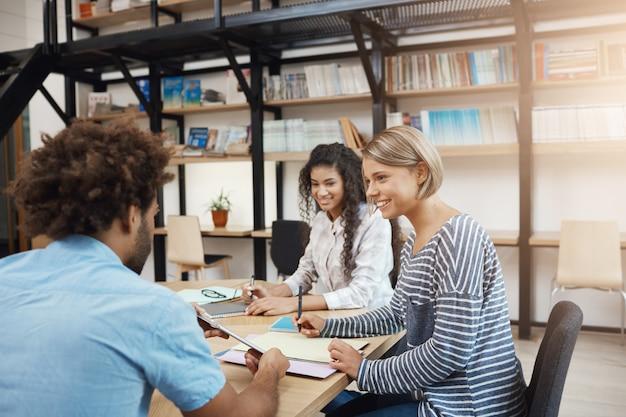 Collaboratief werk. groep jonge projectmanagers die aan nieuwe start, analyseplannen werken. drie perspectief professionele jongeren die in moderne bibliotheek op vergadering zitten. Gratis Foto