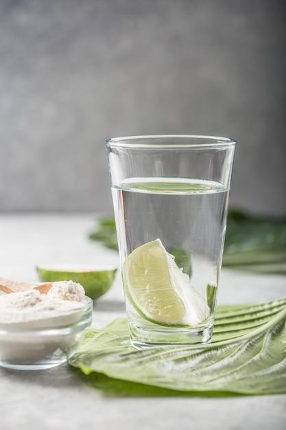 Collageenpoeder en glas water met schijfje limoen; vitamine c . collageensupplementen kunnen de gezondheid van de huid verbeteren door rimpels en droogheid te verminderen. Premium Foto