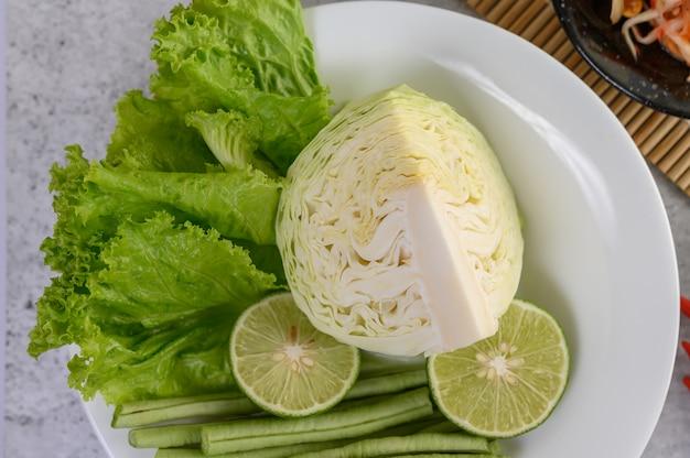 Collard groen, limoen, bonen van de tuin lang en salade op een witte plaat Gratis Foto